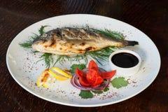 Geroosterde vissen met tomaat, kruiden, uien en citroen Royalty-vrije Stock Foto's