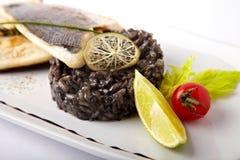 Geroosterde vissen met zwarte risotto Stock Foto's