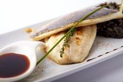 Geroosterde vissen met zwarte risotto Stock Fotografie