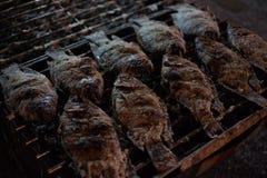 Geroosterde vissen op traliewerk met brand in markt Stock Afbeeldingen