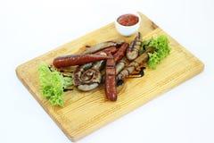 Geroosterde worst op een houten raad met saus, isolatie Stock Afbeeldingen