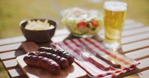 Geroosterde worsten en salades voor een de zomerpicknick stock videobeelden