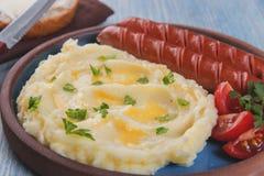 Geroosterde worsten met fijngestampte aardappels dicht omhoog op lijst Stock Foto
