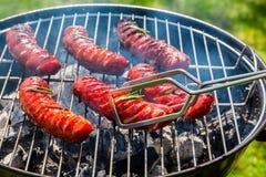 Geroosterde worsten met kruiden en rozemarijn op een grill Stock Foto's