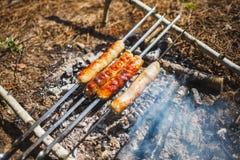 Geroosterde worsten op een kleine brand op een barbecuegrill stock fotografie
