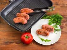 Geroosterde worsten op schotel en grillpan, greens en tomaat stock foto
