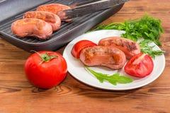 Geroosterde worsten op schotel en grillpan, greens en tomaten royalty-vrije stock fotografie
