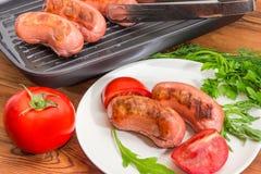 Geroosterde worsten op schotel met greens en tomatenclose-up royalty-vrije stock afbeelding