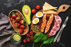 Geroosterde zalm met gekookte ei, ham, groenten en aardbeien op een donkere achtergrond Keto dieetdiner of lunch Hoogste vlakke m royalty-vrije stock fotografie
