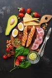 Geroosterde zalm met gekookte ei, ham, groenten en aardbeien op een donkere achtergrond Ketogenic dieetdiner of lunch hoogste men stock foto