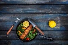 Geroosterde zalmfilet in een pan, groenten, arugula met een citroen royalty-vrije stock foto
