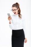 Geïrriteerde woedende jonge bedrijfsvrouw die mobiele telefoon en het schreeuwen gebruiken Stock Afbeeldingen