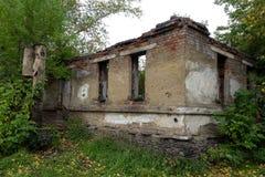 Geruïneerd baksteenhuis in volledige verlatenheid onder de de herfstbomen stock afbeelding