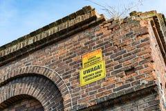 Geruïneerde oude textielfabriek met waarschuwingsbord in Pools Royalty-vrije Stock Afbeelding