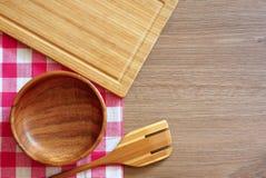 Geruit tafelkleed, houten lepel en een kom op een houten lijst royalty-vrije stock foto's