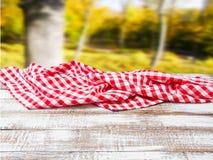 Geruit tafelkleed op oude houten lijst aangaande vage parkachtergrond, vakantieconcept stock afbeeldingen