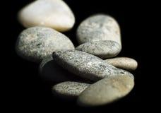 Gerundete Kiesel auf einem schwarzen Hintergrund, Makro Stockfoto