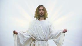Gesù che solleva le mani, sparendo alla luce luminosa di cielo, festa resuscitante archivi video