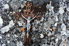 Gesù sul vecchio ed incrocio rotto stagionato che si trova su una pietra con muschio nero Fotografia Stock