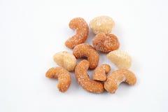 Gesalzene Acajounüsse und Macadamia auf weißem Hintergrund stockfotos