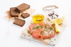Gesalzene Lachse, Brot und Bestandteile auf einem hölzernen Brett Lizenzfreie Stockbilder