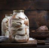 Gesalzene Stücke Schweinefett mit Fleisch werden in den Glasgefäßen geschlossen lizenzfreie stockbilder