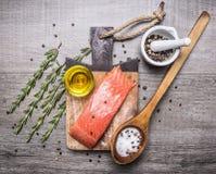 Gesalzenes Lachsfilet auf einem Schneidebrett mit köstlichen Bestandteilen für das Kochen von Draufsicht des hölzernen rustikalen Lizenzfreie Stockfotos