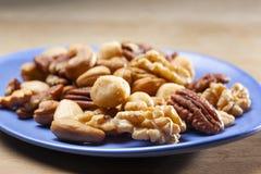 Gesalzte Nüsse mischen auf einem blauen Teller stockfoto