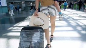 Gesamtlänge der hinteren Ansicht der Zeitlupe der jungen Frau mit kleinem Jungen und großem Koffer gehend in Flughafenabfertigung stock video