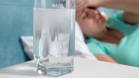 Gesamtlänge der Nahaufnahme 4k des Glases Wassers mit der Auflösung von aspirin-Medikament auf Nachttisch gegen die Frau, die unt stock footage