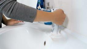 Gesamtlänge der Nahaufnahme 4k des waschenden Badezimmers der jungen Frau singt und des Wasserhahns mit Reinigungsmittel und Schw stock footage
