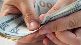 Gesamtlänge der Nahaufnahme 4k von den männlichen Händen, die großen Stapel US-Dollar Rechnungen zählen stock video