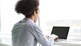Gesamtlänge des jungen lächelnden Mannes, der an Laptop arbeitet stock video footage