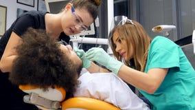 Gesamtlänge eines weiblichen Zahnarztes und ihres Assistenten, die ein junges überprüfen, bemannt Zähne stock video footage