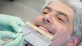 Gesamtlänge eines Zahnarztes, der ein junges überprüft, bemannt Schatten der Zahnfarbe stock video footage