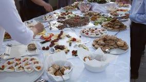 Gesamtlänge einiger Leute, die Lebensmittel auf ihren Platten von einer schwedischen Tabelle nehmen stock footage