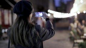 Gesamtlänge HD auf Lager der jungen schönen modernen brunette Frauenstellung auf der Straße an der Nacht und am nehmen Foto od stock video