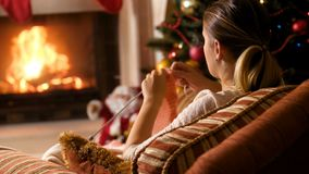 Gesamtlänge 4k der Frau sitzend im Lehnsessel an brennendem Kamin und an strickendem Pullover stock footage