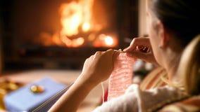 Gesamtlänge 4k der Frau sitzend im Lehnsessel durch den brennenden Kamin und den strickenden woolen Schal stock video footage