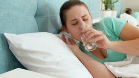 Gesamtlänge 4k der jungen Frau mit den Kopfschmerzen, die im Bett und in Trinkwasser vom Glas liegen stock video footage