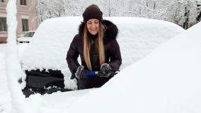 Gesamtlänge 4k der schönen lächelnden jungen Frau, die Schnee von ihrem Automobil mit Bürste entfernt Fahrerreinigungsauto nachhe stock footage