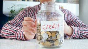 Gesamtlänge 4k des Einsparungsgeldes und -c$werfens des jungen Mannes prägt in Glas moneybox beschriftetem Kredit stock video