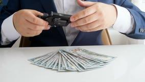 Gesamtlänge 4k des Finanzverbrechers in der Klage, die Gewehr herausnimmt und es auf Stapel Geld setzt stock footage