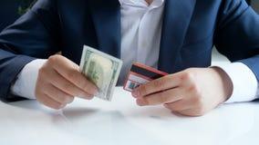 Gesamtlänge 4k des jungen Geschäftsmannes wählend unter Verwendung der Kreditkarte anstelle des Papierdollarscheins Konzept der m stock video footage