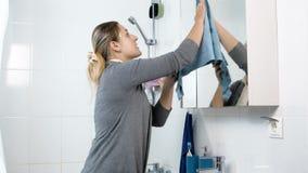 Gesamtlänge 4k des Reinigungsspiegels der jungen Frau im Badezimmer mit blauem Stoff stock video footage