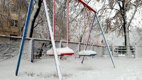 Gesamtlänge 4k des Schwingens auf dem Spielplatz bedeckt im Schnee nach Blizzard am Winter Keine Kinder spielen herum stock footage