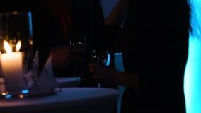 Gesamtlänge von zwei Personen in einem Schatten, der Weingläser hält, nähert sich Tabelle am Nachtklub stock video footage