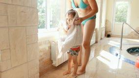 Gesamtl?nge 4k der l?chelnden jungen Mutter, die ihren Kleinkindsohn mit gro?em Tuch nach Klasse im Swimmingpool trocknet und w?r stock video