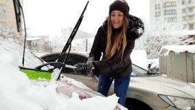 Gesamtl?nge 4k der sch?nen l?chelnden jungen Frau, die Schnee von ihrem Automobil mit B?rste entfernt Fahrerreinigungsauto nachhe stock video footage