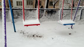 Gesamtl?nge 4k des Schwingens auf dem Spielplatz bedeckt im Schnee nach Blizzard am Winter Keine Kinder spielen herum stock footage